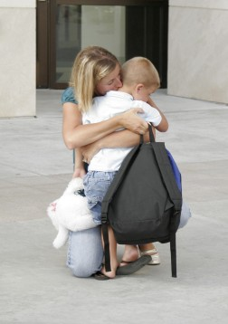 white mom holding little boy with back pack-cropped